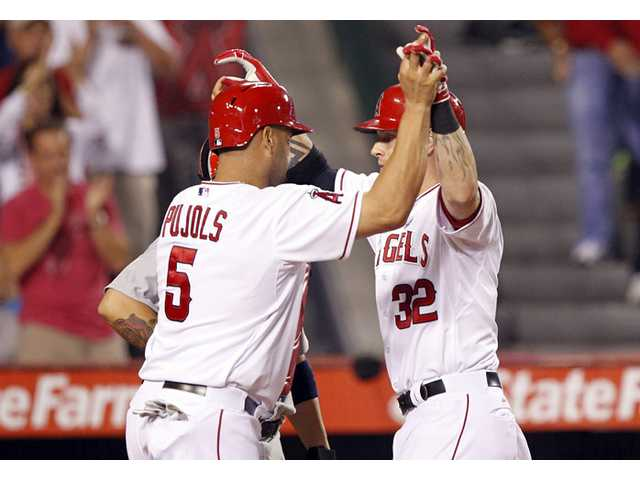 Los Angeles Angel Josh Hamilton, right, greets Albert Pujols at the plate after Hamilton hit a two-run home run on Thursday in Anaheim.