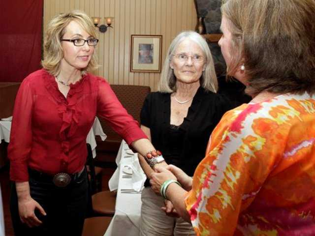 In this photo taken Friday former Arizona Rep. Gabrielle Giffords greets Jackie Barden, right, mother of a Sandy Hook Elementary School shooting victim Daniel Barden, as local supporter Mary Ann Sosnoff, center, looks on at the Orchard Street Chop Shop in Dover, N.H.