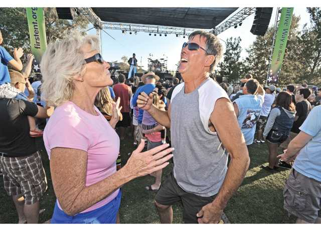 Mary Brunty, left, and Keith Williams dance to the music as Queen Nation performs onstage during the first in the of the 2013 Concert in the Parks series held at Central Park in Saugus on Saturday.