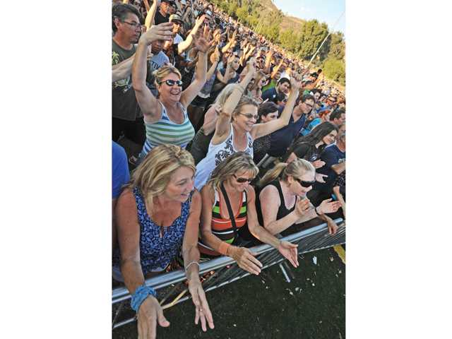 Attendees near the stage cheer as Queen Nation performs before a crowd of thousands during the first in the of the 2013 Concert in the Parks series held at Central Park in Saugus on Saturday.