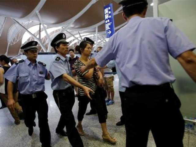 An unidentified family member of one of two Chinese students killed in an Asiana Airlines plane crash on Saturday, is escorted by airport security officers at the Pudong International Airport in Shanghai, China, today.