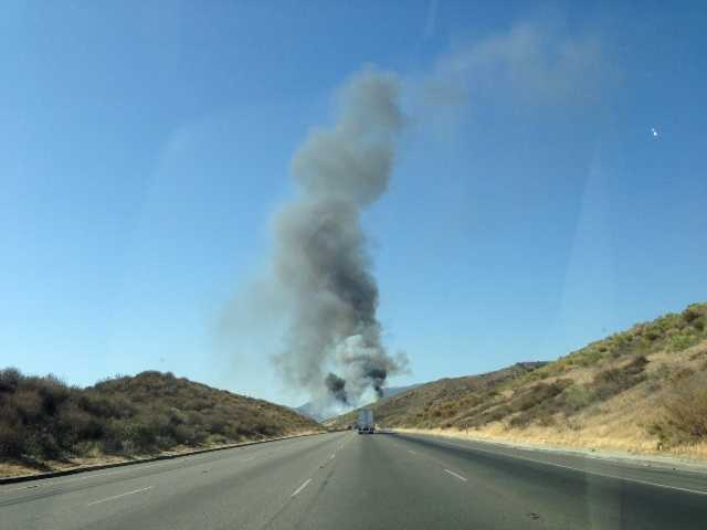 UPDATE: At least 25 acres burned after hay truck sparks brush fire on Interstate 5