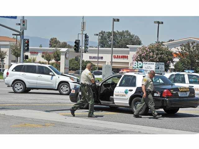 Sheriff's officials walk past a cruiser that was involved in a crash with a Toyota RAV4 on Lyons Avenue at Orchard Village Road in Newhall on Tuesday. Signal photo by Jonathan Pobre