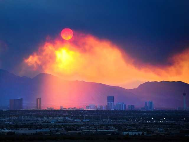 The Las Vegas Strip skyline is seen as smoke continues to billow from the Carpenter 1 fire. Crews are burning away undergrowth within a quarter-mile of homes.
