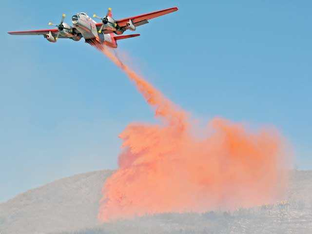 A Lockheed P-2 Neptune aircraft drops fire retardant over the scene of a brush fire east of Interstate 5 north of Templin Highway on Tuesday. Photo by Jonathan Pobre.