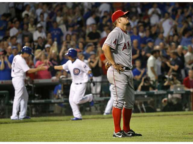 Los Angeles Angels starting pitcher Joe Blanton, right, reacts after giving up a three-run home run to Chicago Cubs' Darwin Barney, background right with third base coach David Bell on Tuesday in Chicago.