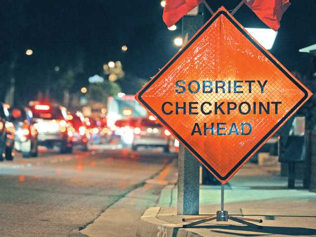 A sign warns driver of a sobriety checkpoint ahead during a DUI checkpoint Thursday night on Lyons Avenue in Newhall. Signal photo by Dan Watson