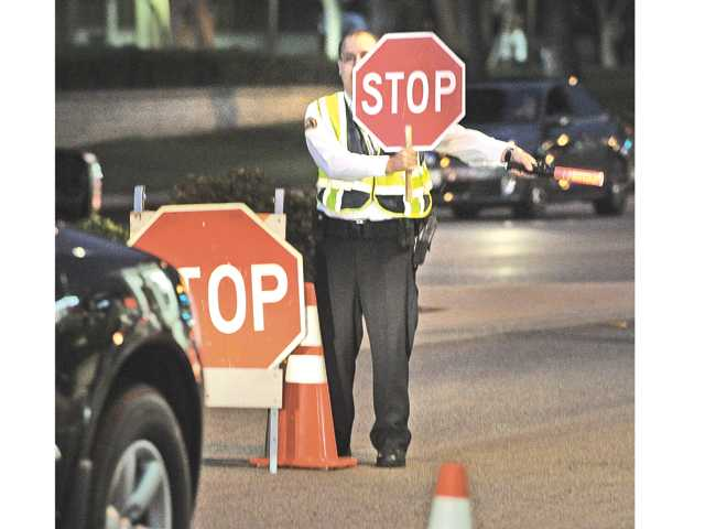 Volunteer On Patrol Jay Schllnick stops cars at a Santa Clarita Valley Sheriff's Department DUI checkpoint Thursday night on Lyons Avenue in Newhall. Signal photo by Dan Watson