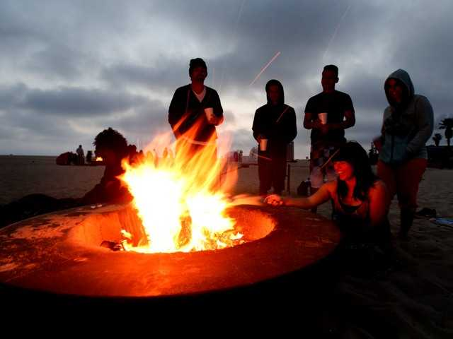 Beachgoers stand around a fire pit on in Huntington Beach in April. Calif. Air quality regulators voted to prohibit fire rings within 700 feet of homes.