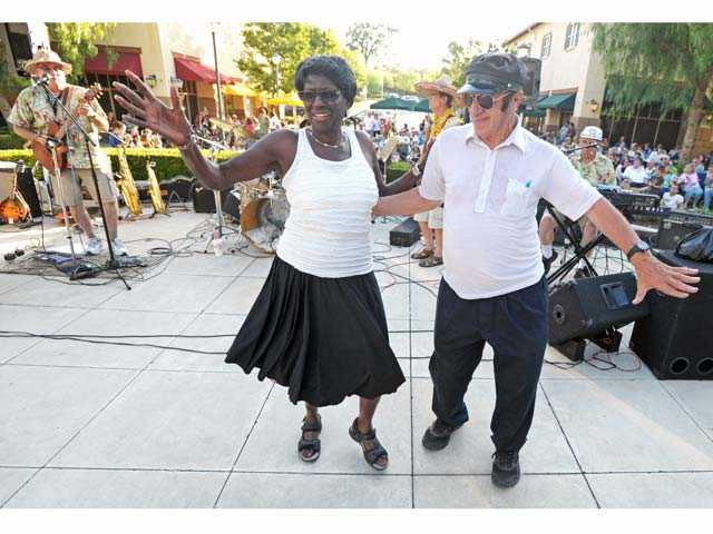 Tommie Ward, left, and Rudy Pavini dance as The Hodads perform at Valencia Marketplace on Friday.
