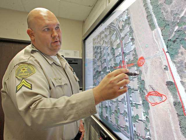 Deputy Josh Dubin shows how a Sheriff's Station smart board is used to track individuals on paseos, which thread through 20 miles of the SCV. Signal photo by Jonathan Pobre