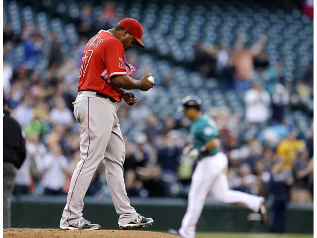 Los Angeles Angels starting pitcher Jerome Williams, left, turns away from the plate as Seattle Mariners' Raul Ibanez rounds the bases behind on a home run Friday in Seattle.