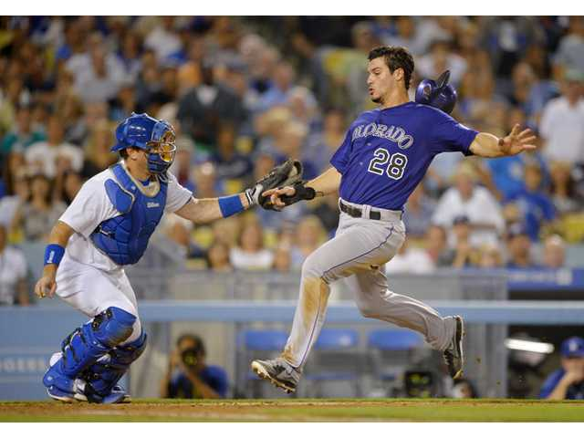 Colorado Rockies' Nolan Arenado, right, scores under the tag of Los Angeles Dodgers catcher A.J. Ellis on a single by DJ LeMahieu during the fifth inning on Friday in Los Angeles.