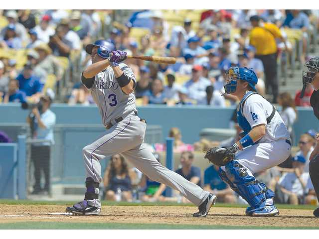 Colorado Rockies outfielder Michael Cuddyer, left, hits a home run as Los Angeles Dodgers catcher A.J. Ellis looks on Sunday in Los Angeles.