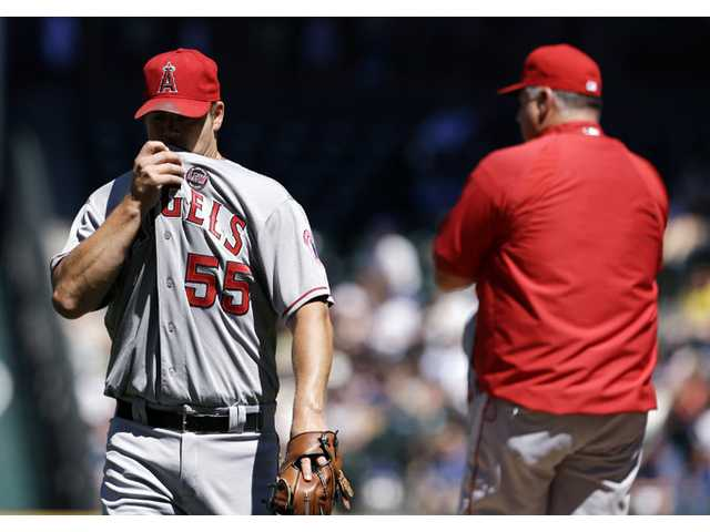 Los Angeles Angels starting pitcher Joe Blanton, left, heads off the field against the Seattle Mariners on Sunday in Seattle.