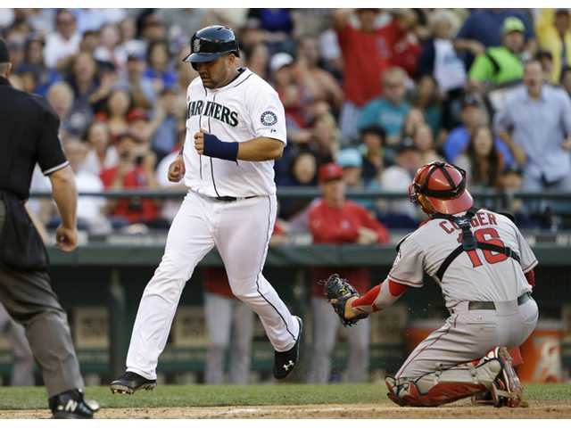 Seattle Mariners' Kendrys Morales, left, scores as Los Angeles Angels catcher Hank Conger turns toward him in the fourth inning Saturday in Seattle.