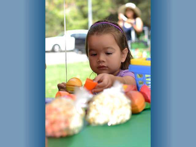 Alex De La Vega plays with the toys in the kids area at the market. Alex and her mother Stacey De La Vega live around the corner and decided to come to celebrate the anniversary and get some fresh air. Photo by Steve Palma for The Signal.
