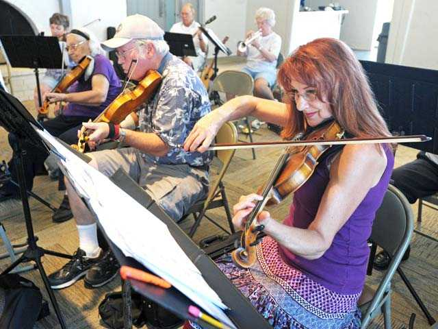 Violinists, from right to left, Heli Sterner, Dave Nul and Mildred Ballace rehearse with the Santa Clarita Valley Senior Orchestra at the Del Prado Homeowners Clubhouse in Newhall on Monday. Signal photo by Jonathan Pobre