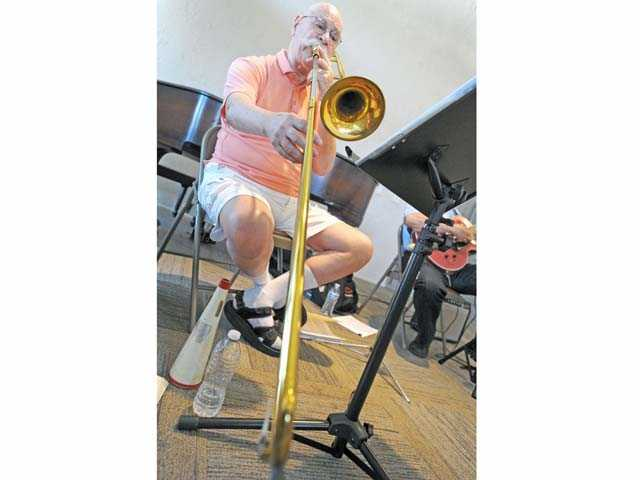Bill Spilka plays the trombone as he leads a rehearsal of the Santa Clarita Valley Senior Orchestra on Monday. Signal photo by Jonathan Pobre