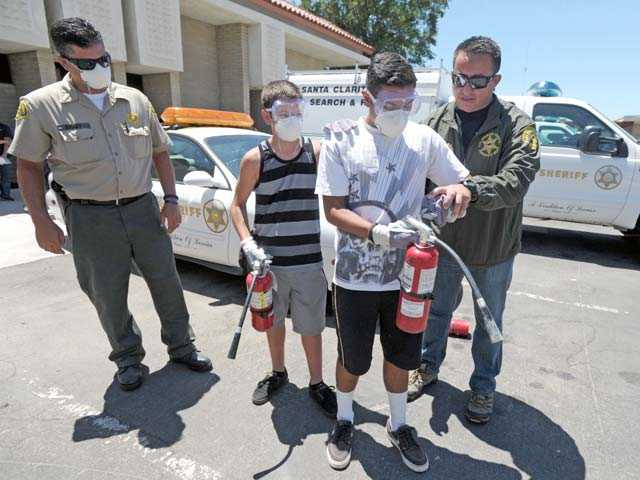 From right to left, Deputy Arthur Valenzuela of the Sheriff's Department's Temple Station guides Gerardo Gonzalez, 16, of Val Verde, and Josh Vizcarra, 12, of Castaic, through the use of a fire extinguisher as Santa Clarita Station Deputy Brian Rooney looks on.