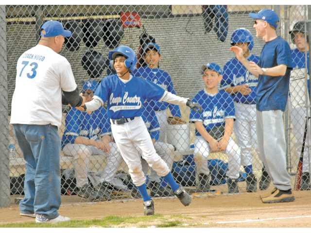 Canyon Country Dodgers manger, Hugo Lopez, left, congratulates base-runner, Victor Ramirez after stealing home base on at Little League opening day at Canyon Country Little League Complex in 2009.