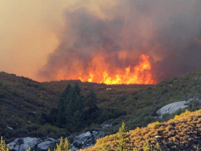 The Mountain Fire burns over a ridgeline near the community of Idyllwild. The fast-moving wildfire doubled in size Tuesday, prompting the evacuation of about 50 homes.