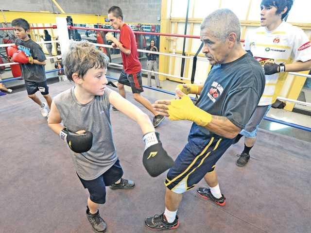 "Classmates work around the ring as Spencer Kurry, 10, left, works with boxing instructor Gilbert Amaro in the third week of the ""boxing introduction for youth"" class for ages 10-17 at the City of Santa Clarita Newhall community Center in Newhall on Tuesday. Photo by Dan Watson."