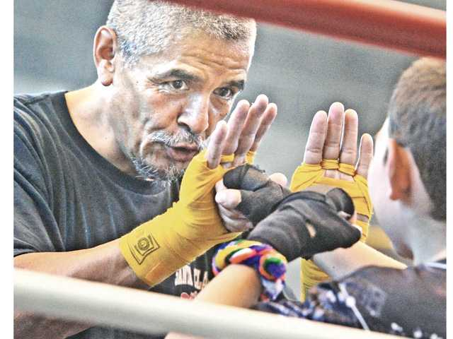 Boxing instructor Gilbert Amaro works with one of the 30 students on a combo punch drill.Photo by Dan Watson.