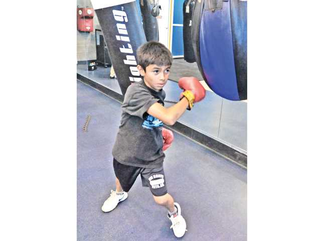 Steven Rosales, 11, hits the heavy bags at the City of Santa Clarita Newhall community Center in Newhall on Tuesday. Photo by Dan Watson.