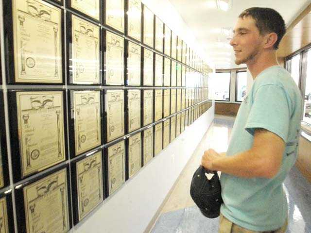 Jacob Landis, 24, looks at a wall of patents as he tours the manufacturing facility of Advanced Bionics in Valencia on Wednesday. Landis is a recipient of a cochlear implant produced by the Valencia company. Signal photo by Jonathan Pobre