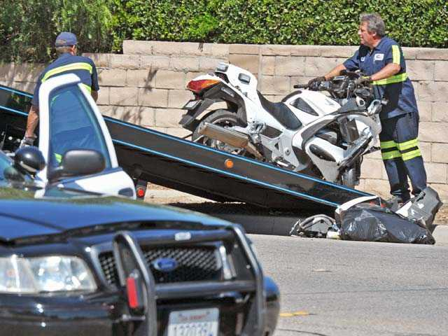 Tow truck drivers move a motorcycle involved in a crash on Whites Canyon Road at Ranier Street in Canyon Country on Wednesday morning. Signal photo by Jonathan Pobre.