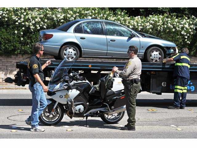 Sheriff's officials work the scene of crash involving a car and a motorcycle on Whites Canyon Road at Ranier Street in Canyon Country on Wednesday morning. Signal photo by Jonathan Pobre.
