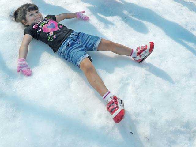 Raquel Lombardi, 4, makes a snow angel.