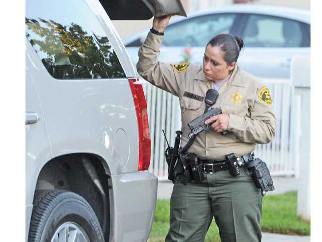 A Santa Clarita Sheriff's deputy searches the back of an SUV as it exits the containment area in Newhall where deputies were conducting a search for a man reportedly armed with a gun. Photo by Dan Watson.