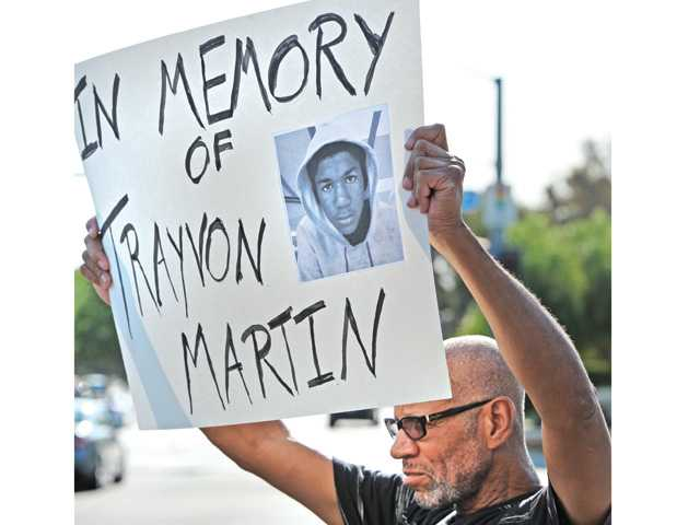 Phillip Jordan of Castaic, one of an estimated 40 attendees, holds up a placard at the corner of McBean Parkway and Valencia Boulevard during a Trayvon Martin vigil in Valencia on Thursday. Signal photo by Dan Watson