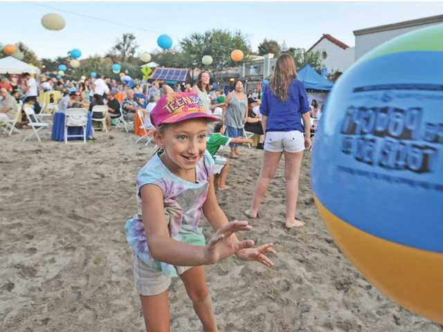 Isabella Smith, 9, of Valencia returns a beach ball as she plays in the tons of sand spread on Main Street in Newhall at the beach party-themed Senses event on Thursday. Photo by Dan Watson.
