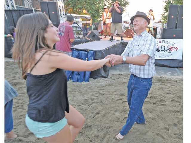Kristy Ewing, left, and Dave Gilman dance barefoot in the sand to the music of Ska Daddyz on Main Street in Newhall on Thursday. Photo by Dan Watson.