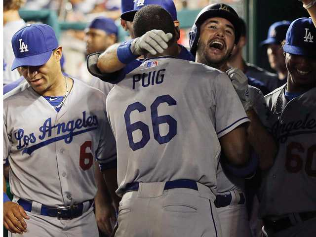 Los Angeles Dodgers Andre Ethier, center, is hugged by teammate Yasiel Puig (66) in the dugout after hitting a solo home run against the Washington Nationals in the ninth inning at Nationals Park on Friday in Washington.