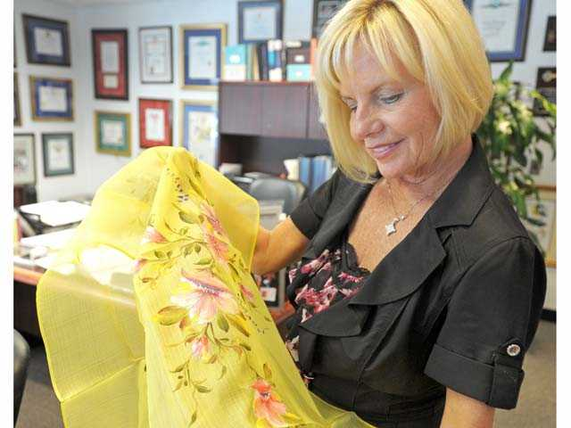 Cheri Fleming, President of Soroptimist International of the Americas, admires a traditional Filipino floral cloth she brought back from her recent trip to the Philippines Spring Conference. Photo by Jonathan Pobre/The Signal.