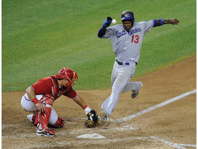 Los Angeles Dodger Hanley Ramirez (13) comes in to score a run on a sacrifice fly by Andre Ethier during the 10th inning Saturday in Washington.