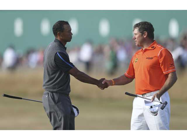 Tiger Woods, left, shakes hands with Lee Westwood on the 18th green after their third round of the British Open Golf Championship at Muirfield, Scotland, Saturday.