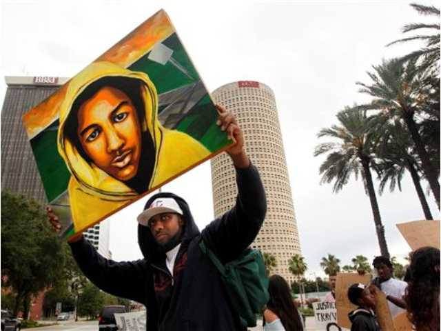 James Brewton, 39, from Brandon, hoists his portrait of Trayvon Martin along with a group of about 175 as they gather at Curtis Hixon Waterfront Park after marching to the federal courthouse in Tampa on Sunday July 14, 2013, to protest after a jury found George Zimmerman not guilty of murder.