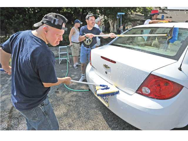 Kawanis Aktion Club members Scott Straus, left, and Mario Hidalgo scrub a car during a car wash event at His Way Community Church in Valencia on Saturday to benefit The Painted Turtle Camp. Photo by Dan Watson