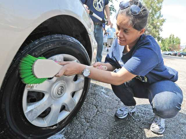 Kawanis Aktion Club members Scott Straus, left, and Mario Hidalgo scrub a car during a car wash event at His Way Community Church in Valencia on Saturday to benefit Painted Turtle Camp. Photo by Dan Watson