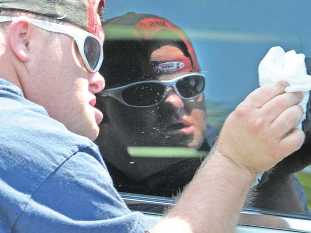 Kawanis Aktion Club member Gerry Haughinberry wipes the window of a car during a car wash event at His Way Community Church in Valencia on Saturday to benefit Painted Turtle Camp. Photo by Dan Watson