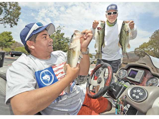 "Twenty- three-year U.S. Navy veteran Gary Briddy, left sits a the controls of a bass boat as he and angler Roger LaRouque hold up some of the big mouth bass they caught during the Top Stick Tour - ""Day on the Lake"" fishing tournament where military veterans were paired with experienced anglers for a day of fishing and barbecue at Castaic Lake on Saturday."