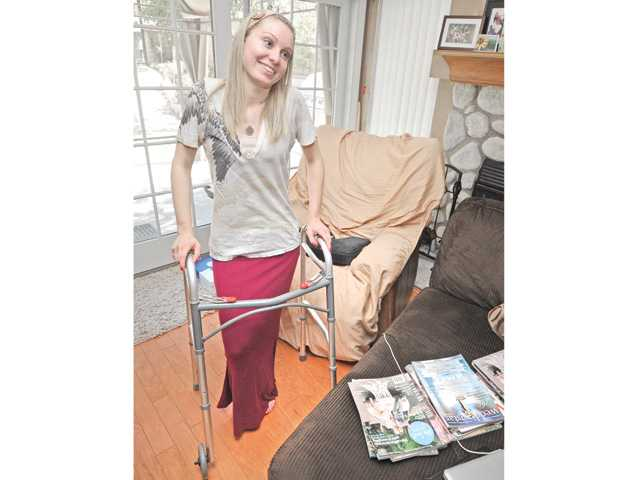 Emalee Banry stands with the help of a walker in the family room of her mother's Castaic home where she has been recovering and planning her September wedding after a near-fatal car crash in May.