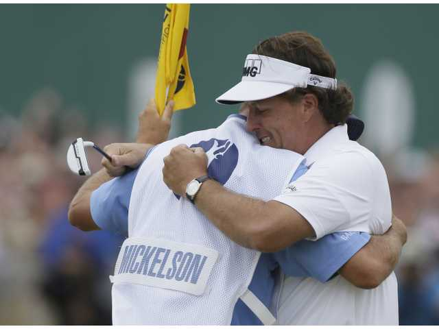Phil Mickelson, right, celebrates after his final putt on the 18th green with his caddie Jim Mackay during the final round of British Open at Gullane, Scotland on Sunday.