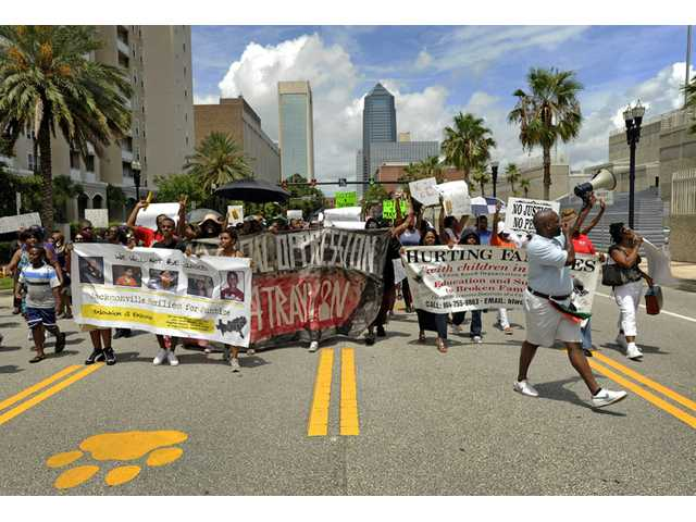 Protesters make their way down Bay Street as they head to the Duval County Jail building to show their support for Marissa Alexander during a protest march in Jacksonville, Fla. on Saturday.