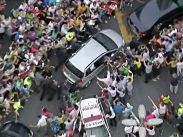 A crowd mobs the silver Fiat carrying Pope Francis through Rio de Janeiro on Monday. Ecstatic believers forced the closed Fiat to stop several times as they swarmed around.